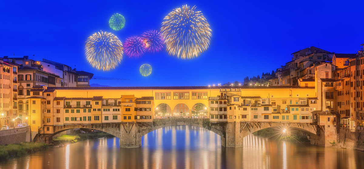The spectacular Ponte Vecchio bridge and Arno River lit up by fireworks over new year.