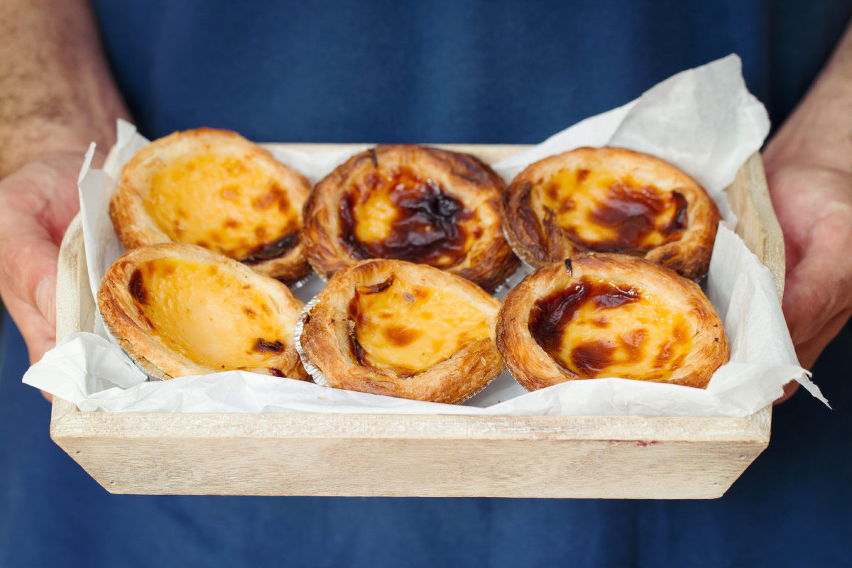 Man holding tray of pasties de nata food bucket list