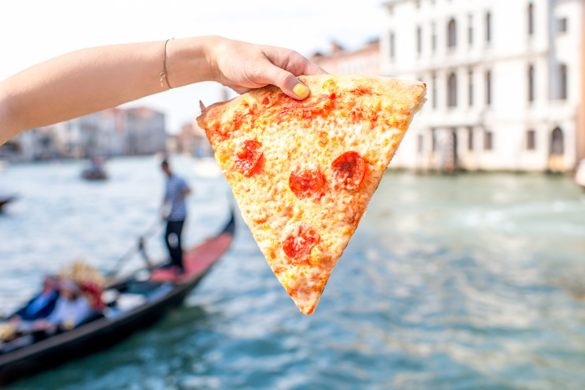 Woman holding pizza in Venice food bucket list