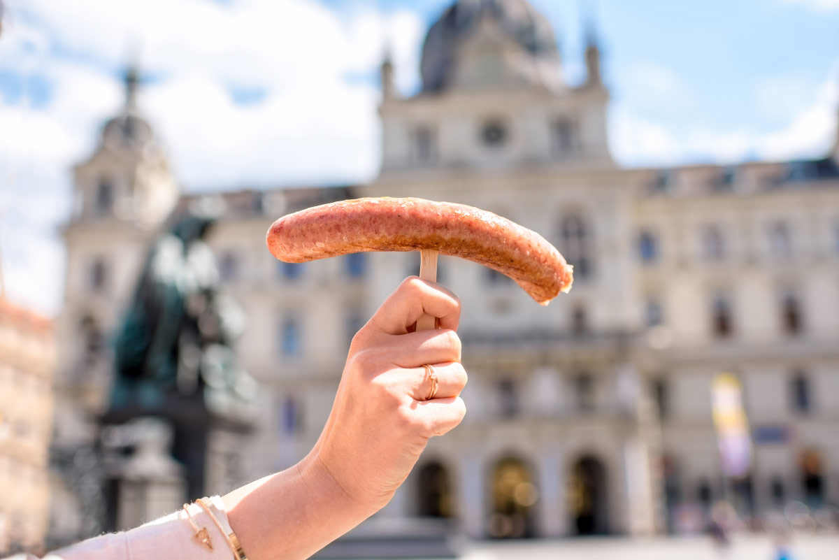 Woman holding wurstel in Vienna, Austria food bucket list