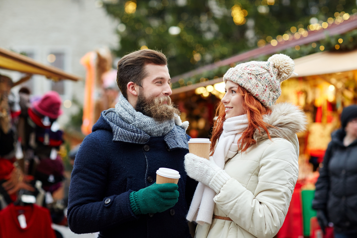 Couple drinking hot chocolate at Christmas Market winter holiday Europe