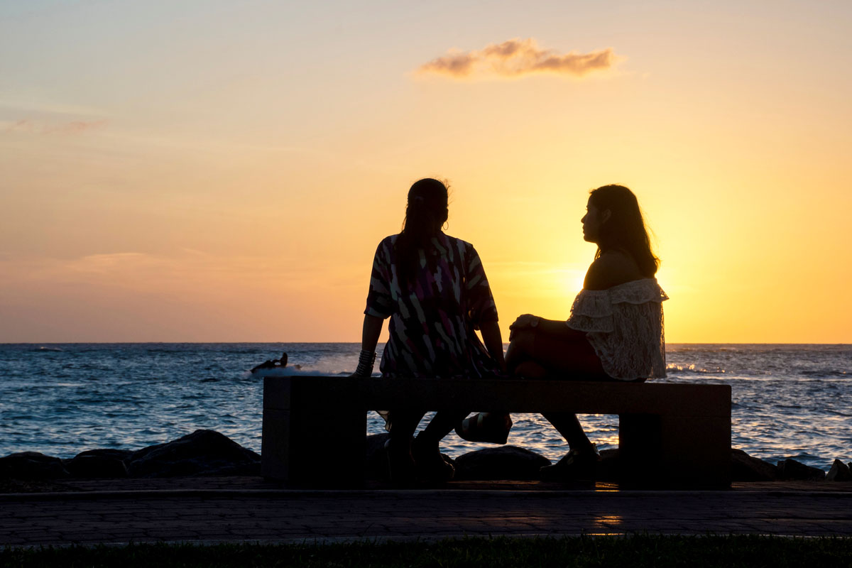 Two friends enjoying the sunset at a beach in Aruba