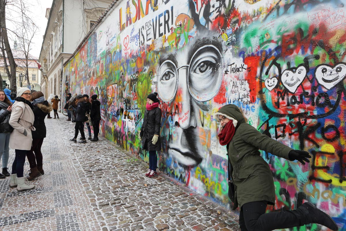 Happy tourists snapping a few amazing pictures at the Lennon wall