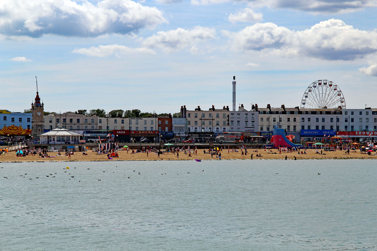 A view of the popular sandy beach with Dreamland's big wheel in Margate