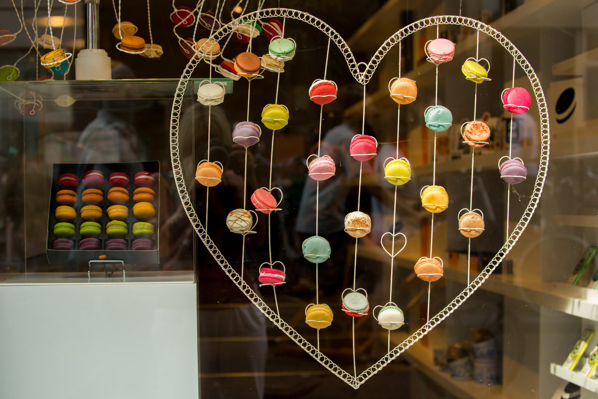 Colourful heart shaped display of macarons in a bakery shop window