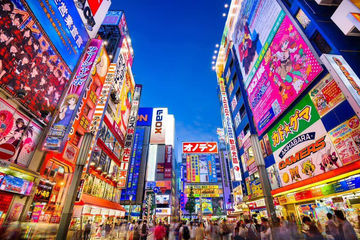 Crowds pass below colorful signs in Akihabara. The historic electronics district has evolved into a shopping area for video games, anime, manga, and computer goods.