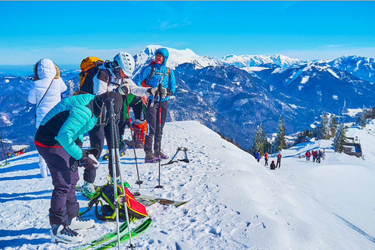 The group of skiers prepares to downhill from the Zwolferhorn mountain peak in Austria
