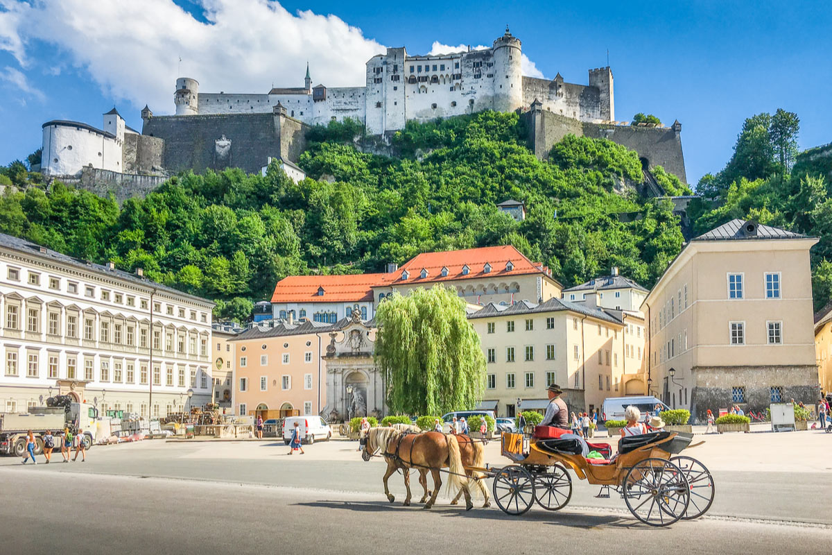 The historic city of Salzburg with traditonal horse-drawn Fiaker carriage and famous Hohensalzburg Fortress