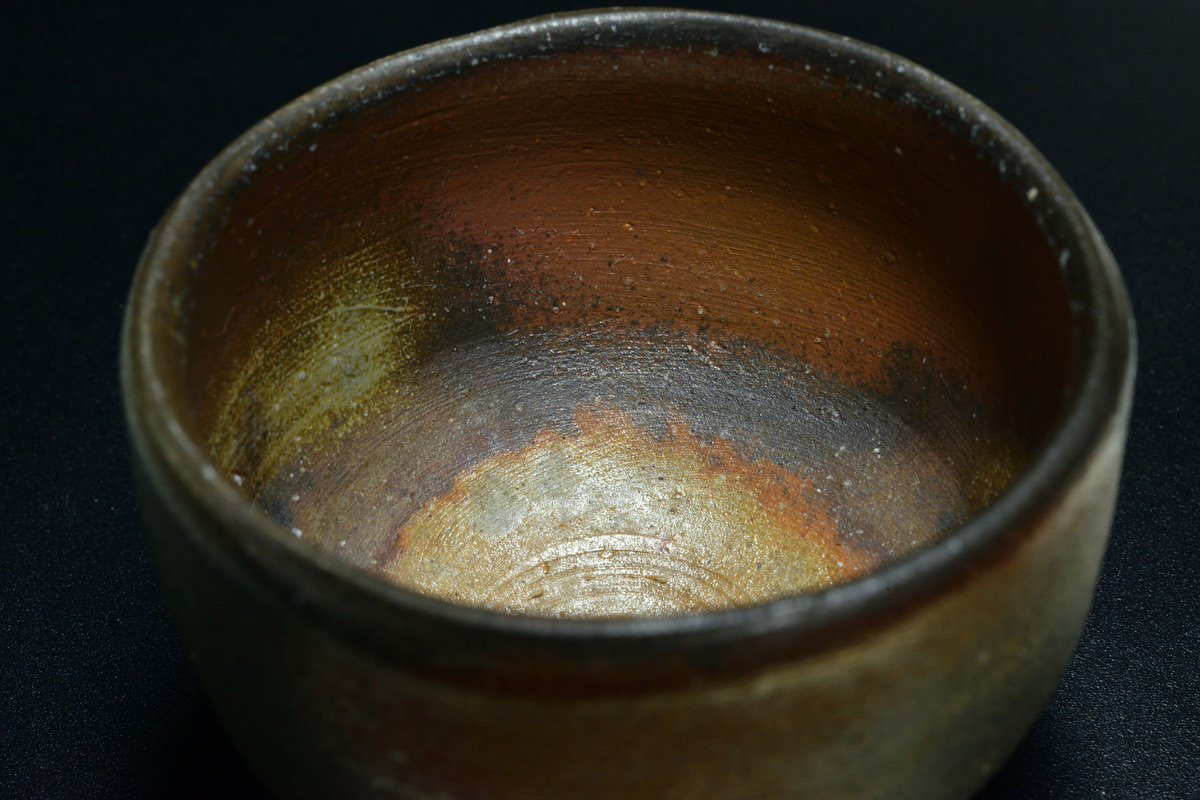 Bizenyaki is characterized by its ironlike hardness, reddish brown color, absence of glaze, and markings resulting from the firing of a wood-burning kiln