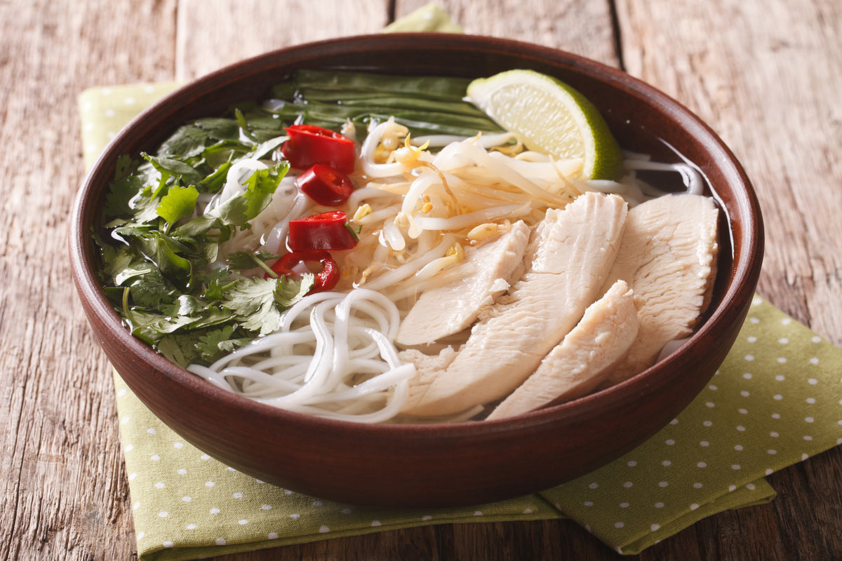 Vietnamese cuisine: soup Pho Ga with chicken, rice noodles and fresh herbs in a bowl