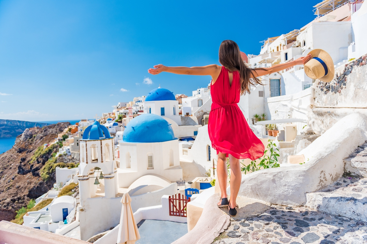 Woman stands near white houses in Santorini Europe