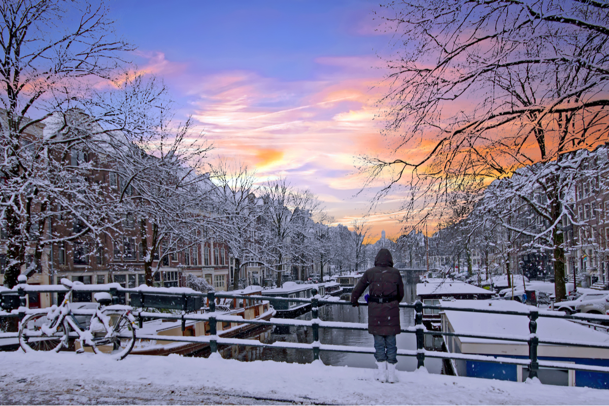 Woman standing on canal bridge in Amsterdam in winter snow