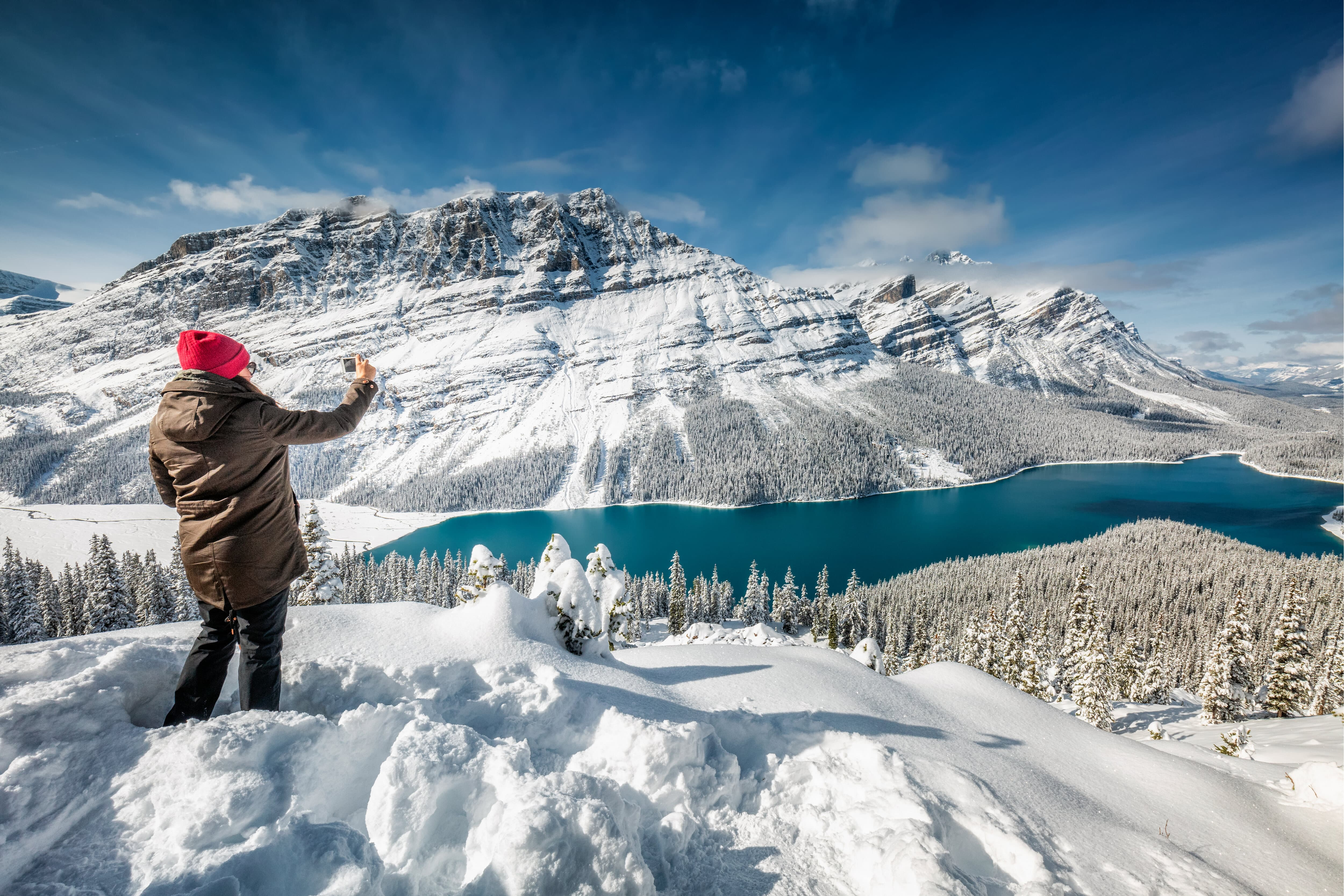 Woman photographing winter landscape in Canada snow