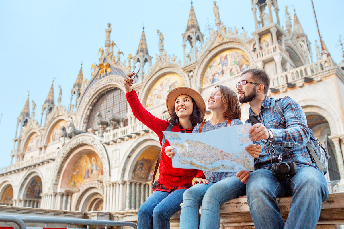 Friends sightseeing St Mark's Square Venice affordable travel