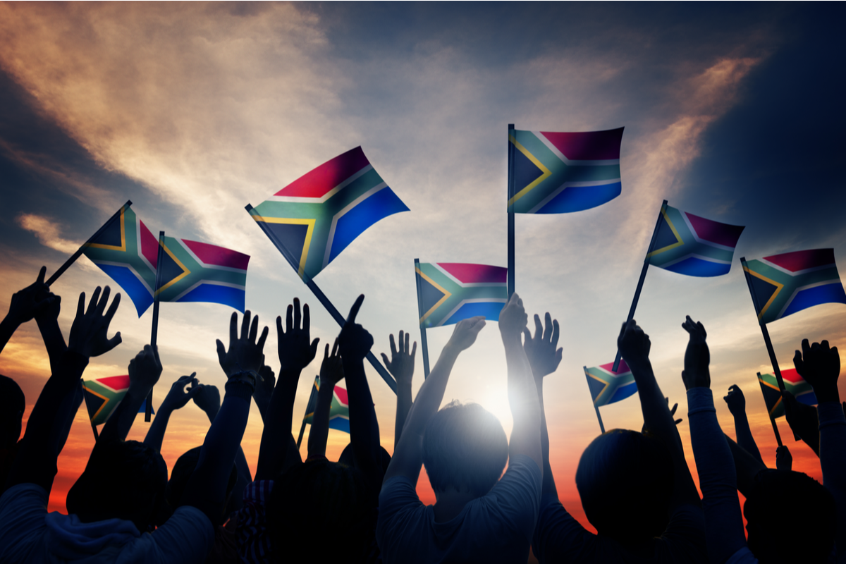People waving south african flags at sunset South Africa