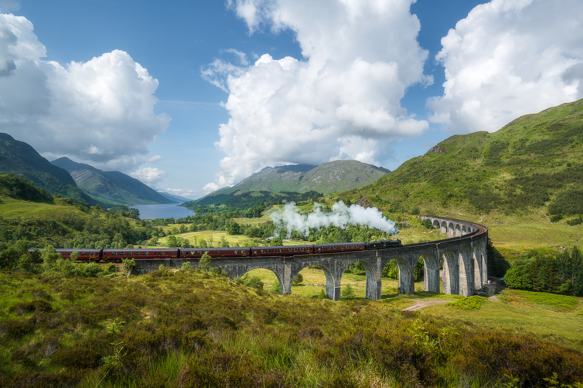 Train crossing Glenfinnan Viaduct in Scotland UK Budget travel