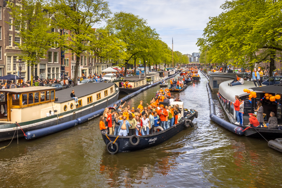 People celebrate on canal boats in Amsterdam King's Day