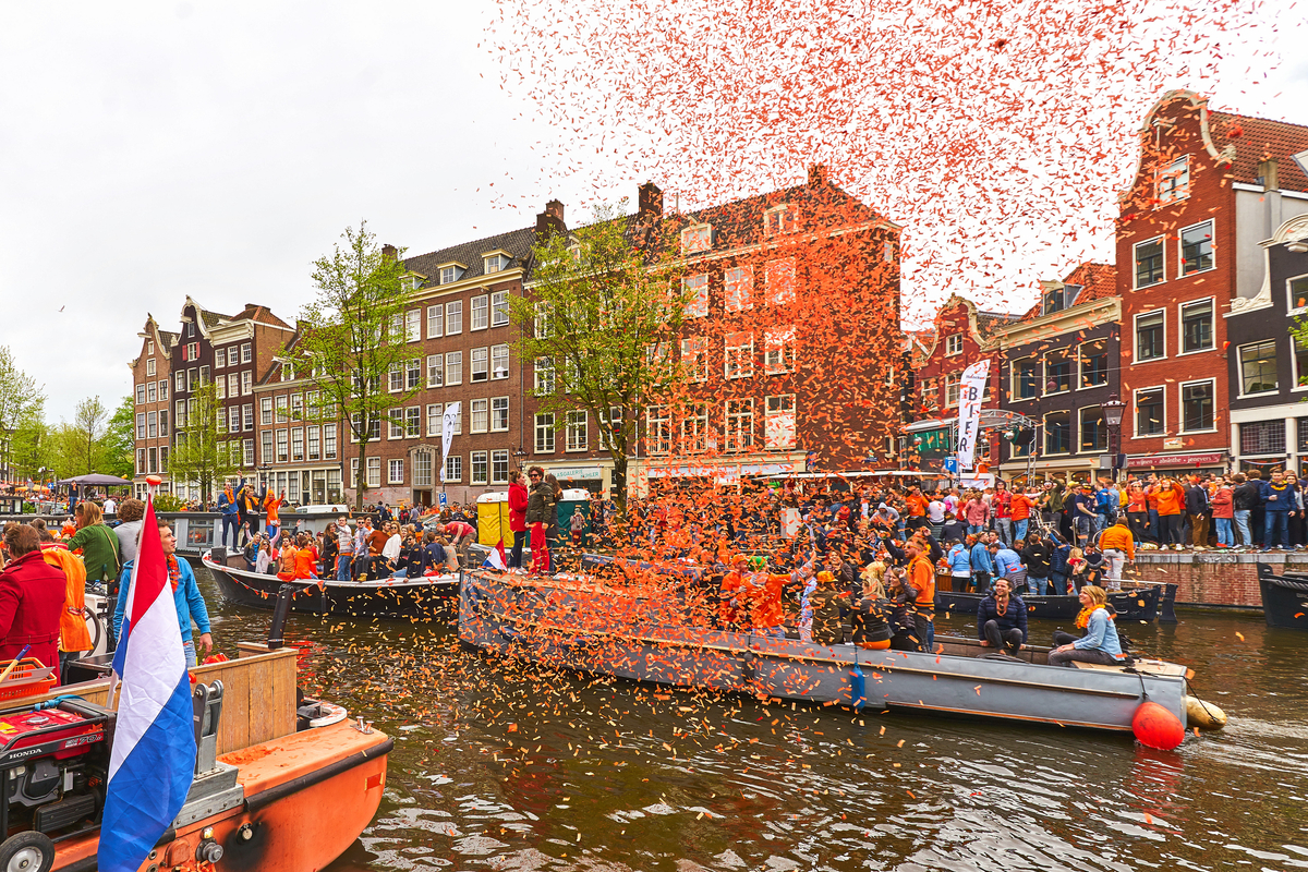 Boats and confetti on canals in Amsterdam King's Day