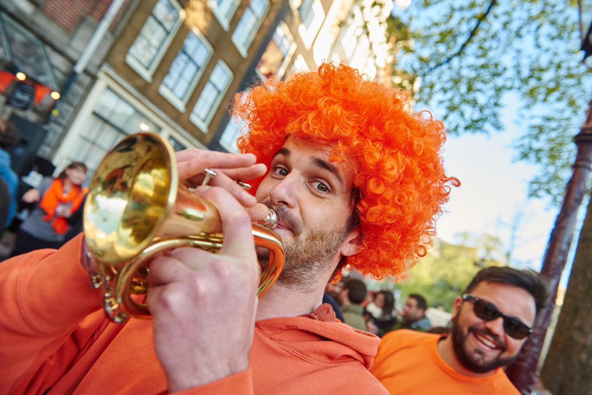 Man playing trumpet and dressed in orange for King's Day