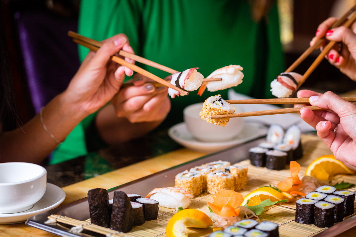 Group of friends share platter of sushi world food & drinks