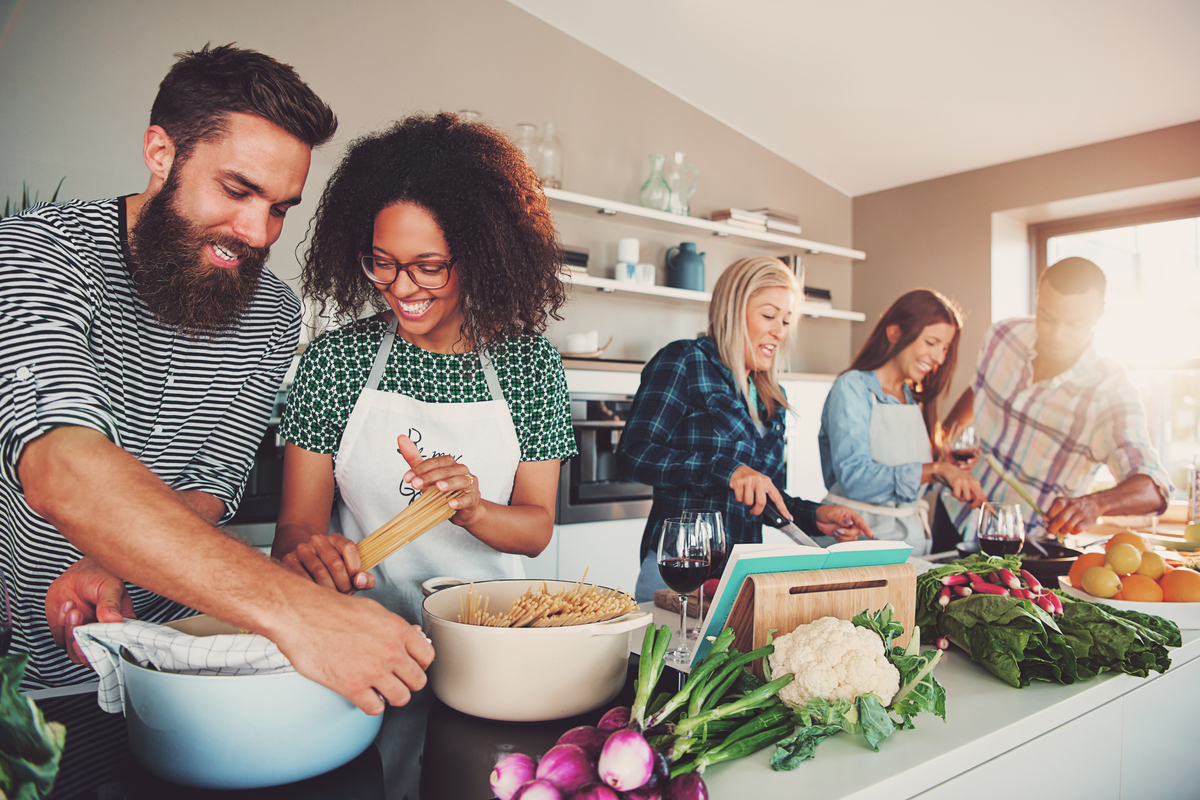 Group of friends cooking in kitchen