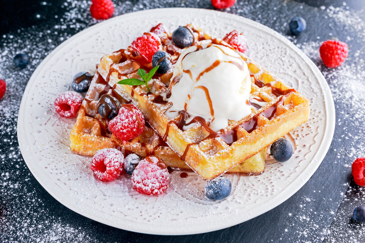 Plate of Belgian waffles woth berries and ice cream World Baking Day