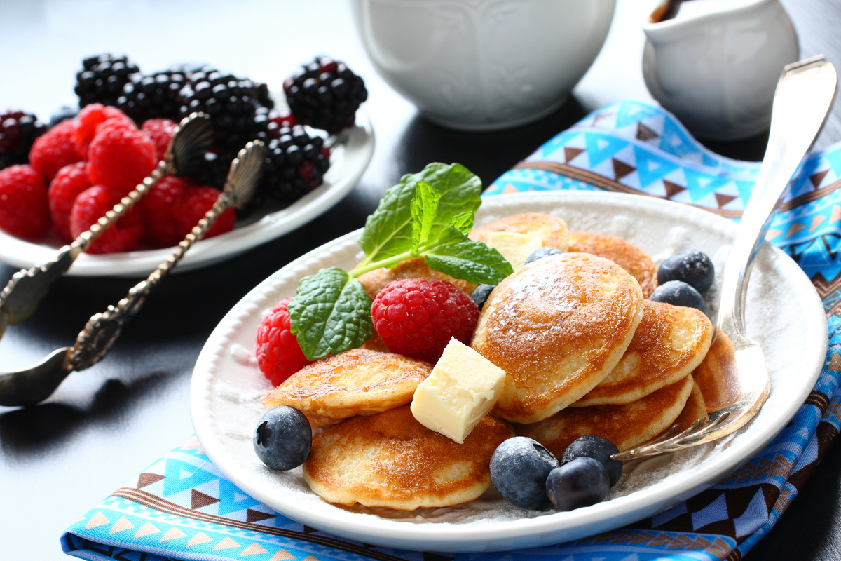 Plate of poffertjes with berries and butter World Baking Day