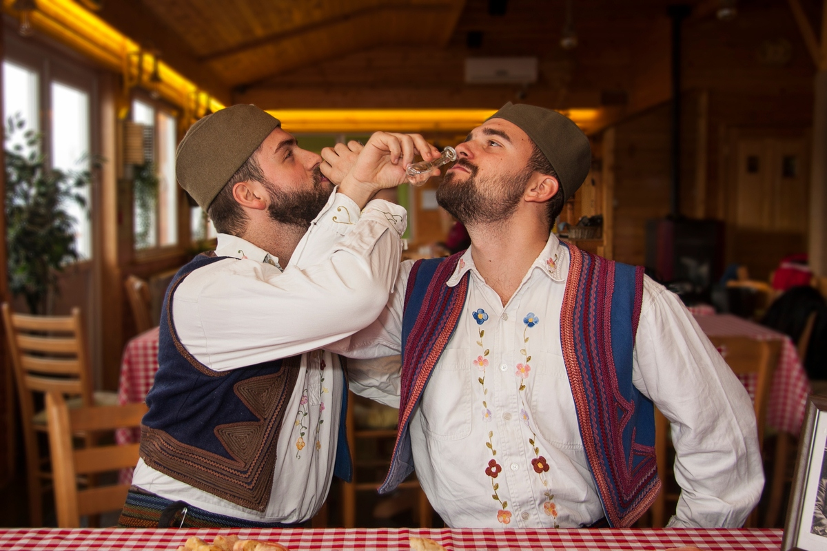 Two men in traditional Serbian outfits drink rakija travelling to Serbia